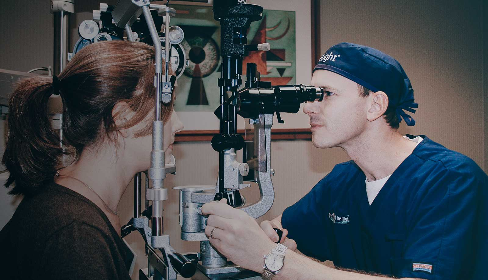 A doctor performing an eye examination to a woman