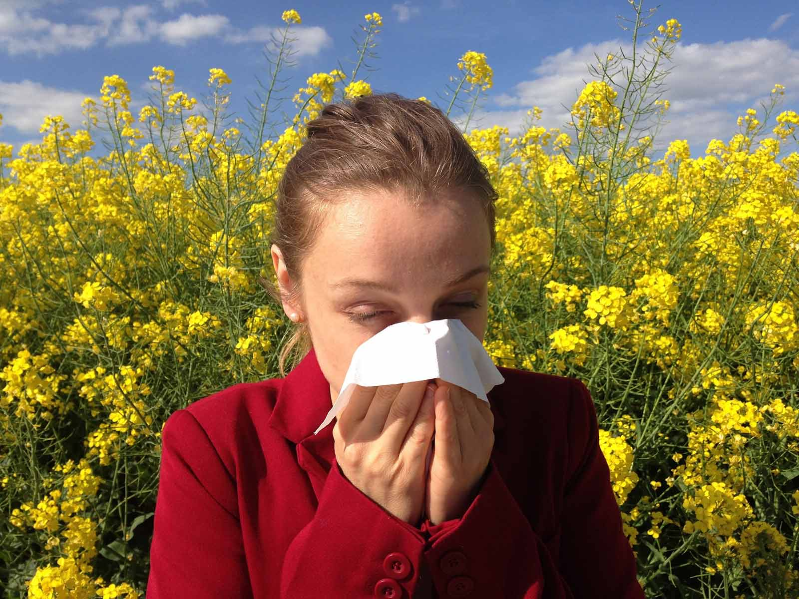 woman sneezing into a tissue with flowers behind her