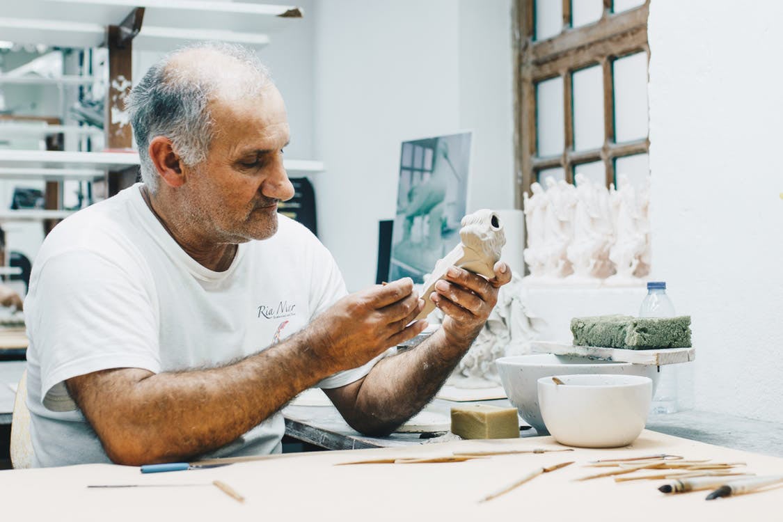 elderly man crafting small statues