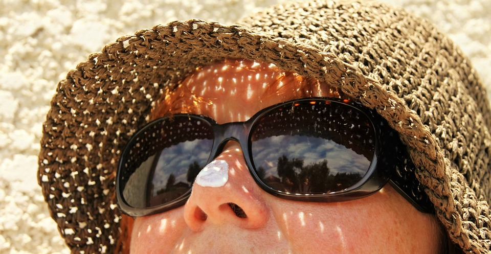 woman wearing sunglasses and a hat looking up