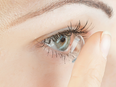 a woman putting in a contact lens
