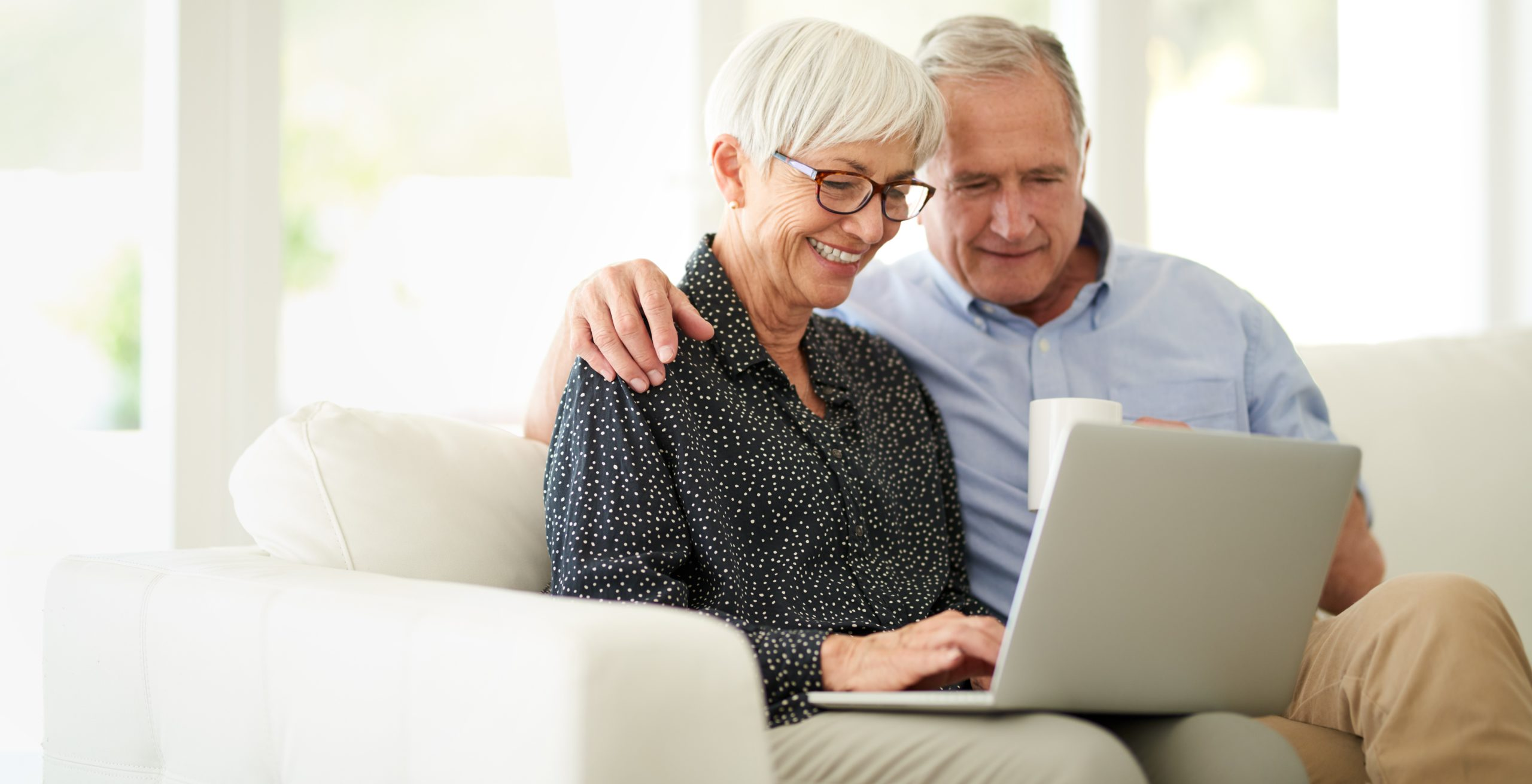 Senior couple sitting on a couch while on a laptop